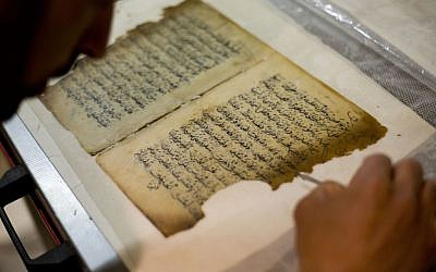 In this photo taken on Monday, Jan. 27, 2014, an employee works on a restoration of an old manuscript at the al-Aqsa mosque compound library in Jerusalem.  (photo credit: AP Photo/Dusan Vranic)