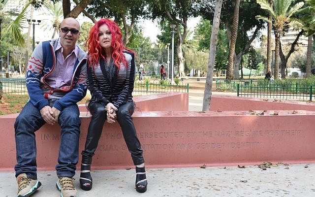 Cyndi Lauper, left, with Israeli journalist, writer and gay rights activist Gal Uchovsky sit on the memorial to gay and lesbian victims of WWII in Tel Aviv, last week (photo credit: courtesy)