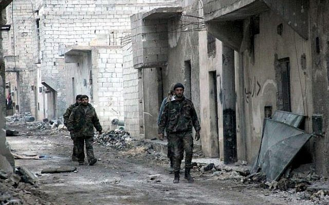 Syrian government forces patrol the Karam al-Qasr district near the Neirab Airport of the northern city of Aleppo, January 26, 2014, in this government agency handout photo (Photo credit: Syrian Arab News Agency/AFP)