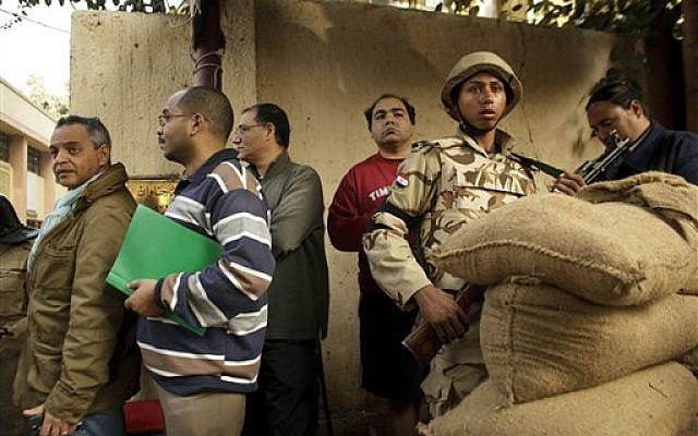 An Egyptian army soldier stands guard as voters line up outside a polling station for the first day in the country's constitutional referendum in the upscale neighborhood of Zamalek in Cairo, Egypt, Tuesday, January 14, 2014.  (photo credit: AP/Maya Alleruzzo)