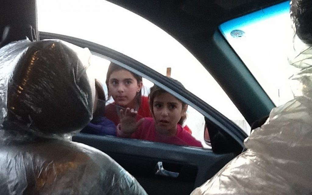 Children peer into Shevet Achim's car in a refugee camp for Syrian Kurds in Iraqi Kurdistan (photo credit: Times of Israel/Lazar Berman)