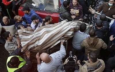 Lebanese citizens carry a covered body from the site of an explosion in a stronghold of the Shiite Hezbollah group at the southern suburb of Beirut, Lebanon, Thursday, Jan. 2, 2014 (photo credit: AP/Hussein Malla)