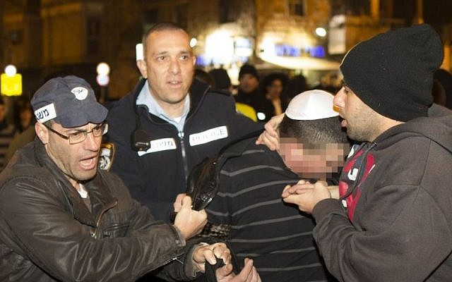 Police detain a protester during a protest at Bar Ilan intersection in Jerusalem on January 8, 2014. (photo credit: Yonatan Sindel/Flash90)