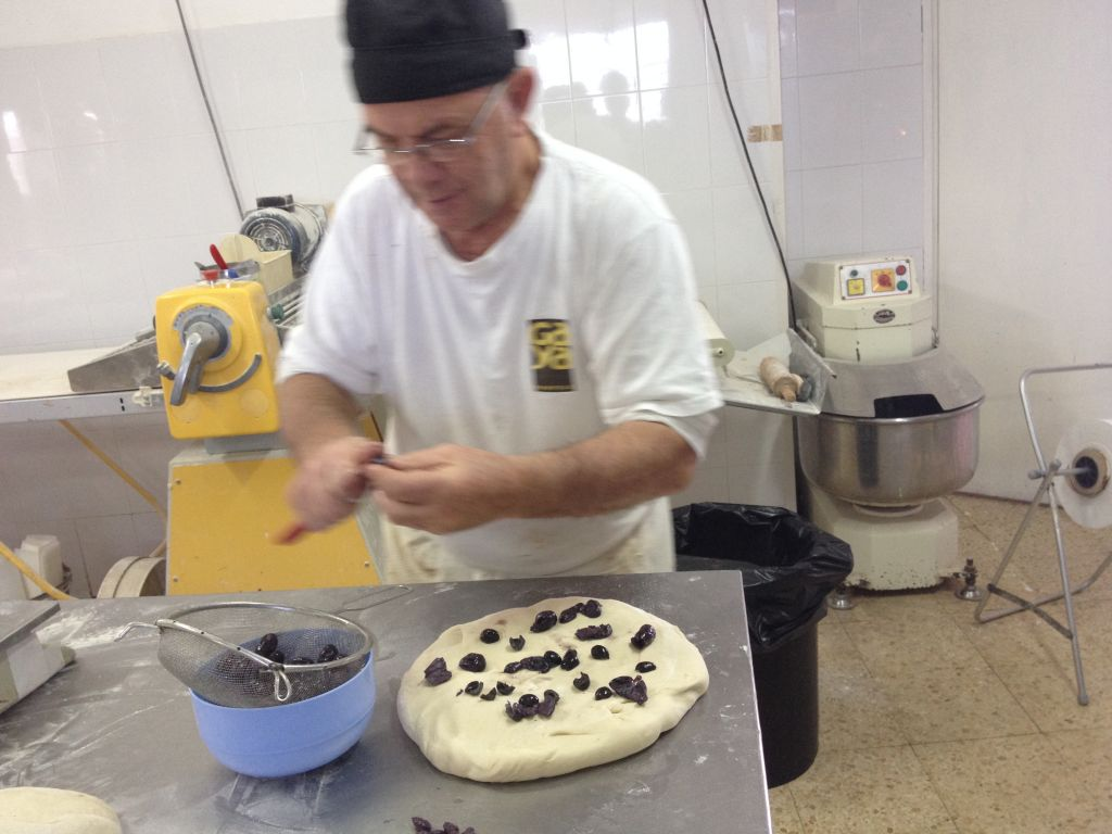 Hans Bertele chopping his olives for a yeasted bread (photo credit: Jessica Steinberg/Times of Israel)
