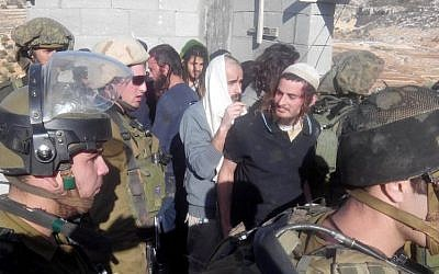 Meir Ettinger, wearing a white skullcap, is escorted by IDF soldiers out of the  West Bank village of Qusra, January 7, 2014. (Rabbis for Human Rights)