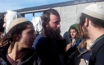 Settlers from the Esh Kodesh outpost, leaving the West Bank village of Qusra, January 7 (photo credit: Zachariah, Rabbis for Human Rights)