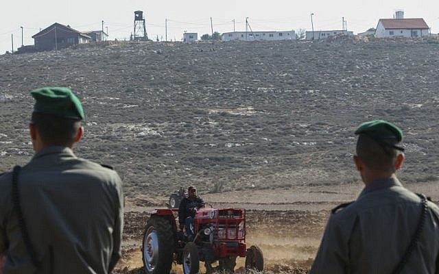 Israeli Border Police officers stand guard as Palestinian farmers use tractors to work the land in the village of Qusra in the West Bank, with the Esh Kodesh outpost in the background, on November 19, 2013. (Nati Shohat/Flash90)
