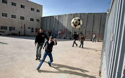 Illustrative: Palestinian schoolchildren playing soccer around the security barrier in the West Bank (Flash 90)