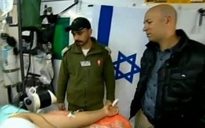 Israeli soldiers treat a wounded Syrian man at a secret military field hospital in the Golan Heights. (photo credit: screen capture, Channel 2)