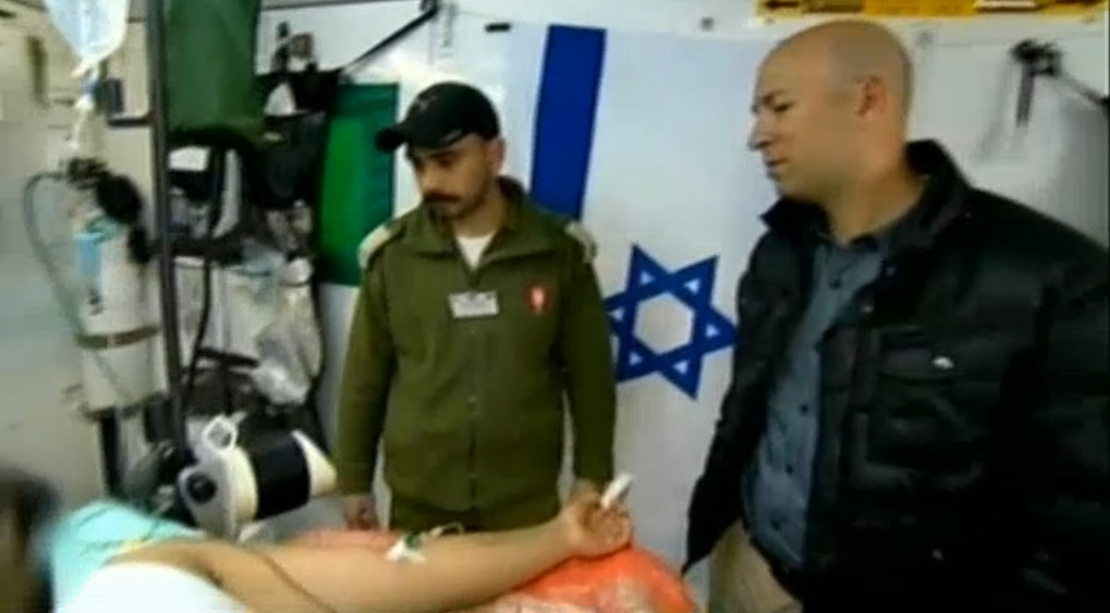 Illustrative: Israeli soldiers treat a wounded Syrian man at a secret military field hospital in the Golan Heights. (photo credit: screen capture, Channel 2)