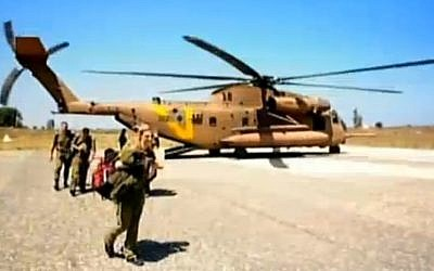 Israeli soldiers disembark from a helicopter en route to a secret military hospital on the border with Syria. (photo credit: screen capture, Channel 2)