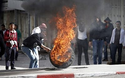 Palestinians set fire to tires during a large protest in Hebron in February (photo credit: Thomas Coex/AFP)