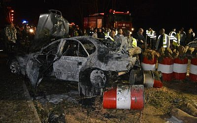 Lebanese emergency personnel and security forces gather around a burnt out vehicle at the site of a bomb explosion that targeted an army post on February 22, 2014 in eastern Lebanon's town of Hermel. (Photo credit: AFP/STR)