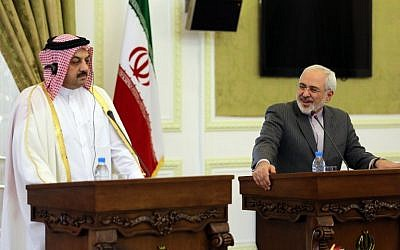 Qatar's Foreign Minister Khalid al-Attiyah (left) holds a joint press conference with his Iranian counterpart Mohammad Javad Zarif on February 26, 2014 in Tehran. (photo credit: AFP/Atta Kenare)