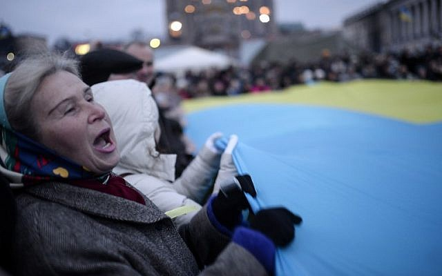People wave a giant Ukrainian flag on Kiev's Independence Square on February 23, 2014. (photo credit: AFP/ BULENT KILIC)