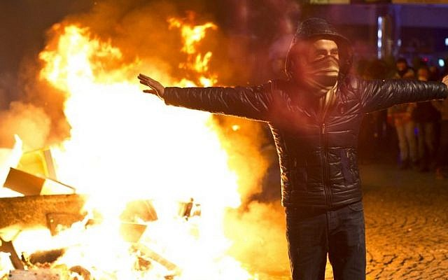 A protester gestures in front of a fire during a protest against corruption in Istanbul, Turkey, on February 25, 2014 (photo credit: Gurcan Ozturk/AFP)