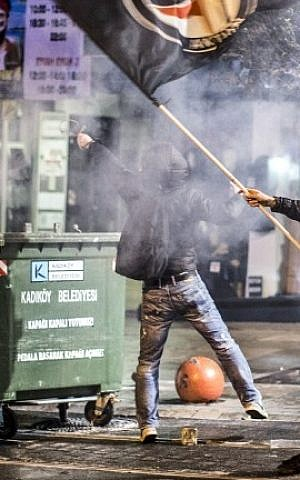 A protester waves a flag as another fires a slingshot from behind trash bins as they clash with riot police during an anti-government protest in Istanbul, Turkey, on February 25, 2014 (photo credit: Gurcan Ozturk/AFP)