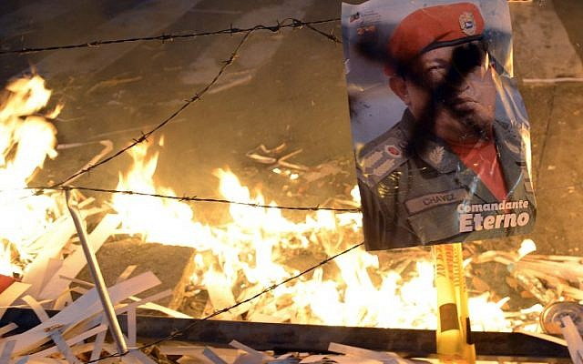 A poster of Venezuelan late President Hugo Chavez remains near a burning barricade during an anti-government demo, in Caracas on February 21, 2014. (photo credit: AFP/Leo Ramirez)