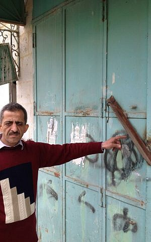 Zidan Sharabati points to the iron bar welded to his shop doors on Shuhada street, February 23, 2014 (photo credit: Elhanan Miller/Times of Israel)