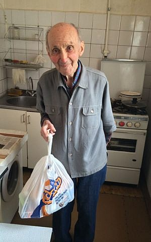 Mihail Solomonovich holding a food package delivered by JDC in the kitchen of his modest one-bedroom apartment in downtown Kiev. (photo courtesy of the JDC)