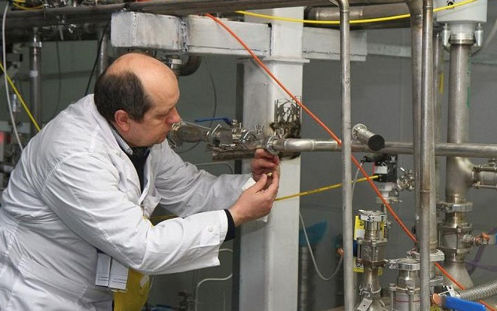 An International Atomic Energy Agency inspector disconnects the connections between the twin cascades for 20% uranium production at Natanz nuclear power plant south of Tehran on January, 20, 2014 (Photo credit: Kazem Ghane/IRNA/AFP)
