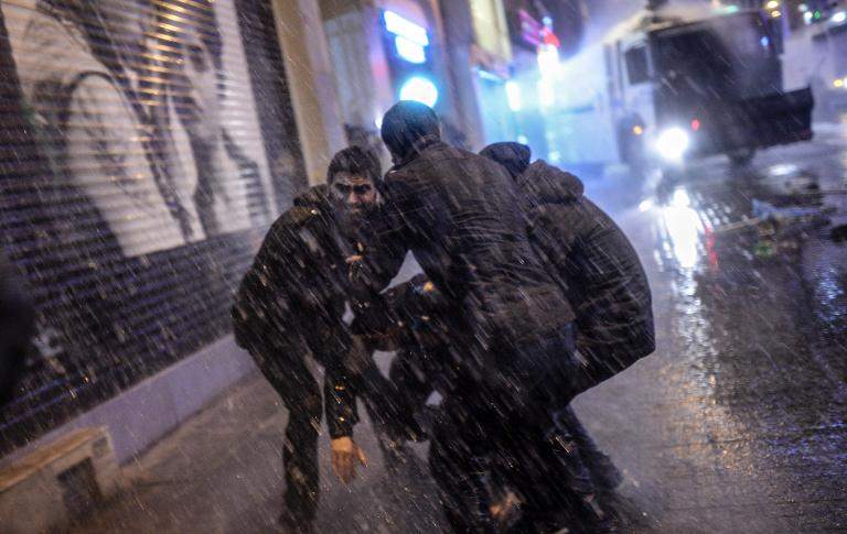 Three men try to lift a protester from the pavement while Turkish anti-riot police trucks use water cannon during a protest against Turkish government's proposed restrictions on the use of Internet, on Istiklal avenue in Istanbul, on Saturday, February 8, 2014 (photo credit: AFP Bulent Kilic)
