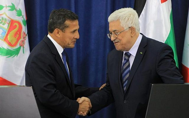 Palestinian Authority President Mahmud Abbas (R) and Peruvian President Ollanta Humala shake hands after a joint press conference in the West Bank city of Ramallah, on February 18, 2014 (photo credit: Pool/AFP Abbas Momani)