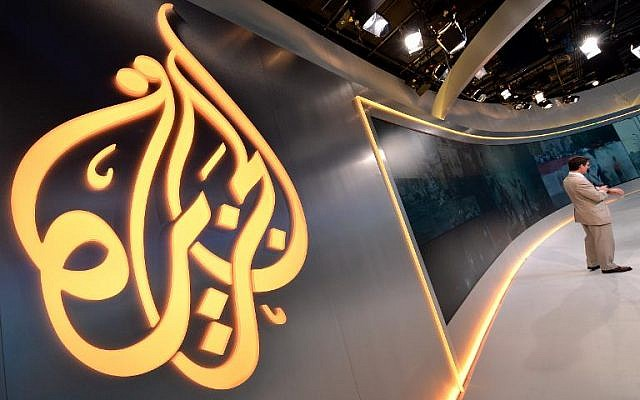 The Al Jazeera logo is seen in the new Al Jazeera America television broadcast studio on West 34th Street on August 16, 2013 in New York as Paul Eedle (R), Deputy Launch Manager for Programming speaks to media during a tour (photo credit: AFP/Stan Honda)