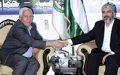 Hamas leader Khaled Meshaal, right, shakes hands with Fatah official Azzam al-Ahmad during their meeting in Damascus, Syria, September 2010 (photo credit: AP/Bassem Tellawi)