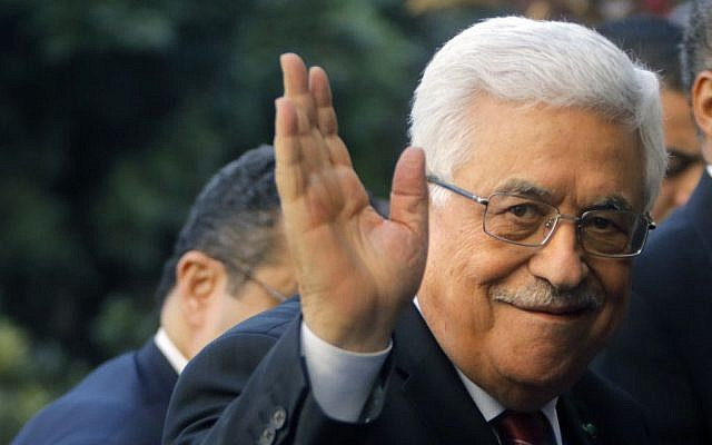 Palestinian Authority President Mahmoud Abbas greets reporters as he arrives at Arab League headquarters in Cairo, Egypt, Saturday, Dec. 21, 2013 (photo credit: AP/Amr Nabil)