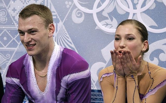 """Evgeni Krasnopolsky, left, and Andrea Davidovich sit in the """"kiss and cry"""" area and await their scores after completing a short program in Sochi, Russia, on Tuesday (photo credit: AP/Darron Cummings)"""