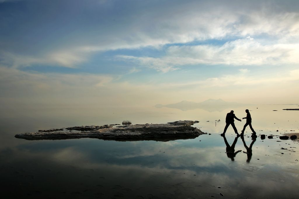 In this Saturday, Feb. 15, 2014 photo, two men walk toward salt-covered rocks that were once deep underwater at Lake Oroumieh. (photo credit: AP Photo/Ebrahim Noroozi)