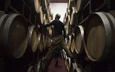 In this photo from February 11, 2014, Israeli workers inspect barrels in a winery in the West Bank settlement of Psagot. (AP/Dan Balilty)