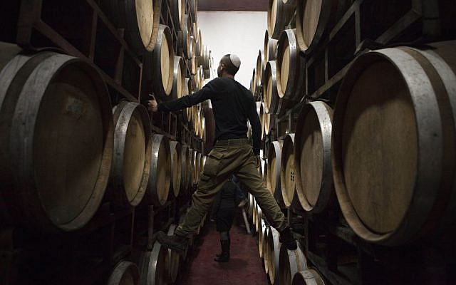 In this Tuesday, February 11, 2014 photo, Israeli workers inspect barrels in a winery in the West Bank settlement of Psagot. (photo credit: AP/Dan Balilty)