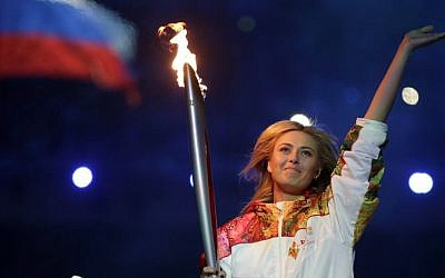 Russia's Maria Sharapova carries the torch during the opening ceremony of the 2014 Winter Olympics in Sochi, Russia, Friday, Feb. 7, 2014. (photo credit: AP/Matt Dunham)