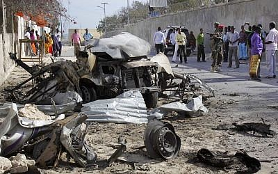 Somalis gather near the wreckage of one of the vehicles used for a car bomb, following a terrorist attack on the presidential palace in Mogadishu, Somalia Friday, Feb. 21, 2014. (photo credit: AP/Farah Abdi Warsameh)