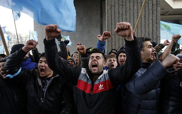 Crimean Tatars shout slogans during a protest in front of a local government building in Simferopol, Crimea, Ukraine, Wednesday, Feb. 26, 2014. (photo credit: AP Photo/Darko Vojinovic)