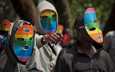 Kenyan gays and lesbians and others supporting their cause wear masks to preserve their anonymity and one holds out a condom, as they stage a rare protest, against Uganda's increasingly tough stance against homosexuality and in solidarity with their counterparts there, outside the Uganda High Commission in Nairobi, Kenya on February 10, 2014. (photo credit: AP/Ben Curtis)