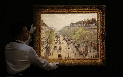 A Sotheby's employee poses with a painting entitled 'Le Boulevard Montmartre, matinee de printemps' by Camille Pissarro on display at the auction house in London, Wednesday, Jan. 29, 2014. (AP Photo/Sang Tan)