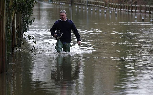 A man wades through a flooded road, in Shepperton, England, Tuesday, Feb. 11, 2014 (photo credit: AP Photo/Sang Tan)