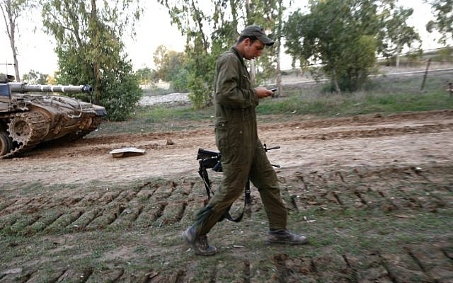 A member of a tank crew checking his phone during Operation Cast Lead, December 2008. (photo credit: Miriam Alster/Flash90)