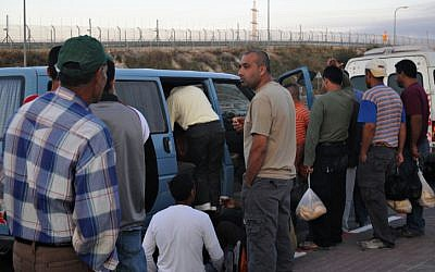 Palestinian workers in 2009, having crossed through Maccabim checkpoint on foot, en route to jobs in Israel (photo credit: Jorge Novominsky/ Flash 90)