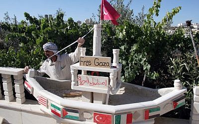In this 2010 photo, a Palestinian in the city of Hebron builds a miniature ship to show support for the flotilla to Gaza, which became the Mavi Marmara incident.  Israel has offered new compensation to Turkey to normalize the strained relations from the incident (photo credit: NAJEH HASHLAMOUN/FLASH90)