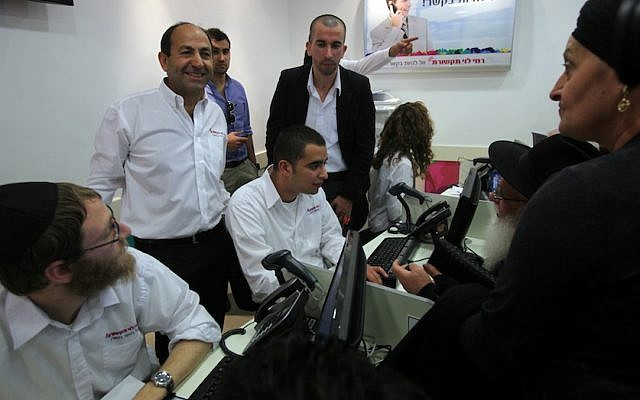 Rami Levy (standing, left) at a cellphone sales center in one of the supermarkets bearing his name. (photo credit: Yossi Zamir/Flash90)
