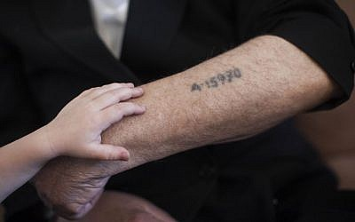 A little boy puts a hand on his grandfather's arm near his concentration camp prisoner number tattoo, in Jerusalem on May 24, 2013. (photo credit: Yonatan Sindel/Flash90)