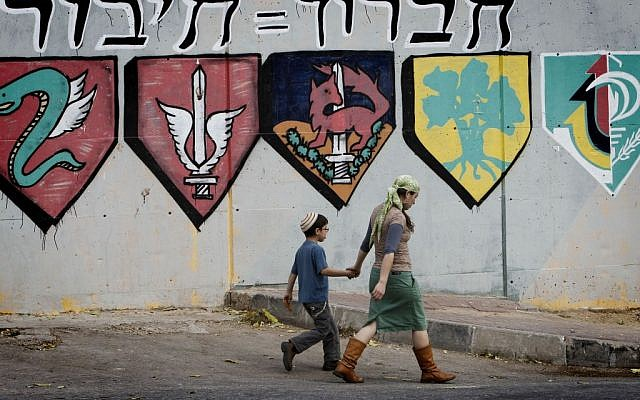 Israeli settlers walk by an IDF base in Hebron that will be partially removed in order to compensate for a new apartment complex for settlers. (Miriam Alster/FLASH90)