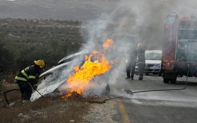 A car hit by a Molotov cocktail outside Tekoa in November 2013. A mother and child were wounded in the attack (photo credit: Gershon Elinson/ Flash 90)
