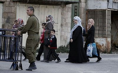 Arab women walk by an Israeli soldier patrolling in the divided West Bank city of Hebron. (photo credit: Miriam Alster/Flash90)