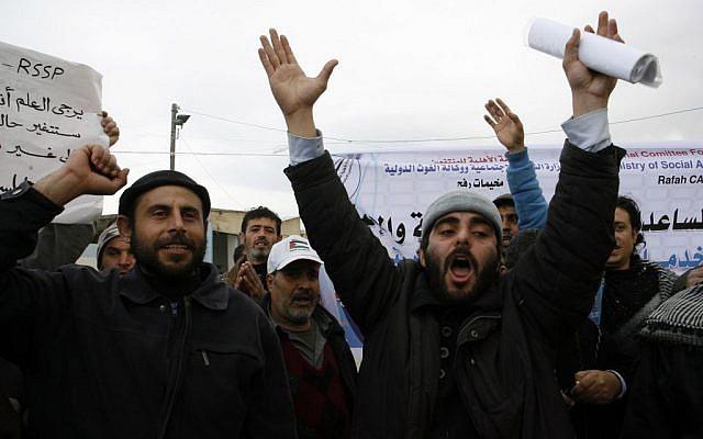 Palestinians protest in front of the UNRWA headquarters against their decision to reduce aid in the Rafah refugee camp in the southern Gaza Strip, on January 26, 2014 (photo credit: Abed Rahim Khatib/Flash90)