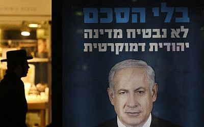 An ultra-Orthodox man walks by a sign showing a picture of Prime Minister Benjamin Netanyahu, on Jerusalem's Jaffa Road, on Monday, January 27, 2014. The sign reads 'Without a deal, we cannot promise a Jewish, democratic state,' a reference to the ongoing peace talks with the Palestinian Authority. (photo credit: Nati Shohat/Flash 90)
